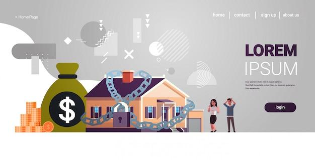 Hombre mujer pareja mirando atado a casa por deuda de cadena de hierro para la casa crisis financiera negocio de tasas de hipoteca bancarrota concepto horizontal de longitud completa