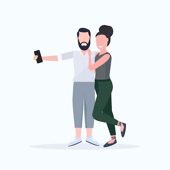 Hombre mujer pareja tomando foto selfie en la cámara del teléfono inteligente personajes de dibujos animados femeninos masculinos abrazando posando sobre fondo blanco de cuerpo entero
