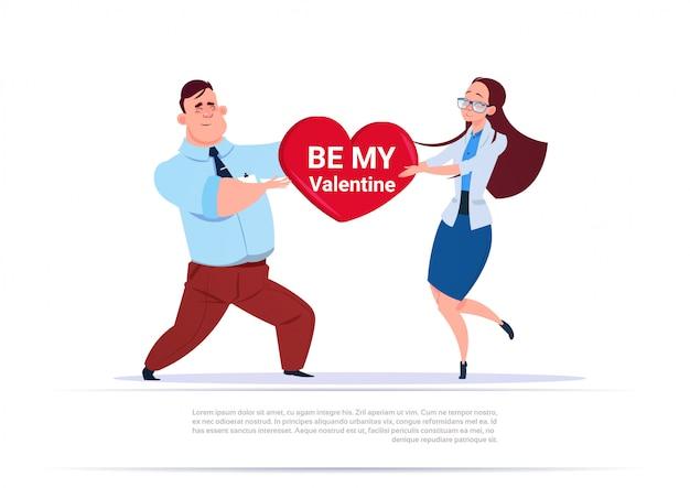 El hombre y la mujer que llevan a cabo forma del corazón con sean mi concepto del día de fiesta del día del amor del saludo de la tarjeta del día de san valentín