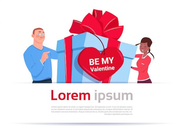 El hombre y la mujer sostienen la caja de regalo con be my valentine greeting tag en forma de corazón en la plantilla fondo blanco