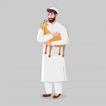 Hombre musulmán que sostiene una cabra marrón en posición de pie sobre fondo gris.