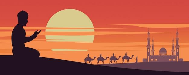 Hombre musulmán reza mientras la caravana musulmán monta camello a mezquita