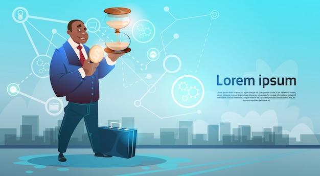 Hombre de negocios afroamericano mantenga el reloj de arena plazo límite concepto de gestión de tiempo