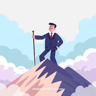 Hombre de negocios con un baston en la cima de una montaña