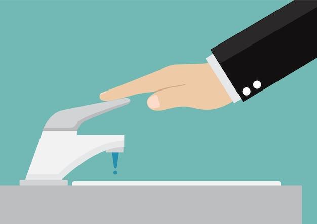 El hombre de negocios cierra el grifo de la mano para ahorrar agua.