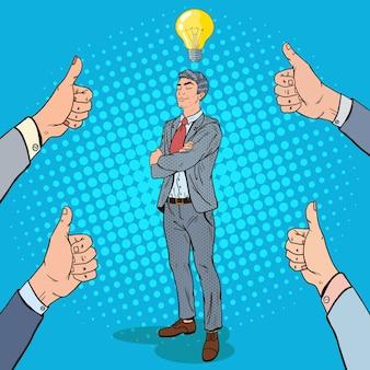 Hombre de negocios confiado del arte pop con la bombilla de la idea y las manos que muestran los pulgares para arriba.