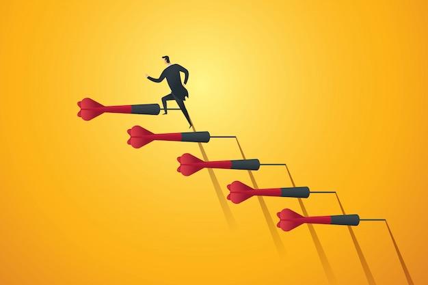 Hombre de negocios corriendo por las escaleras dardos hacia el objetivo y el éxito.
