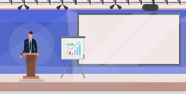 Hombre de negocios del discurso de la tribuna del hombre de negocios que hace la presentación financiera en la reunión de la conferencia con el rotafolio interior moderno horizontal plano de la sala de reunión