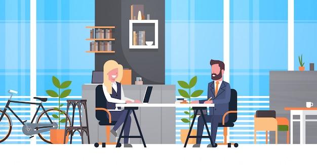 Hombre de negocios en entrevista de trabajo con el gerente femenino de hr, dos hombres de negocios que se sientan en el escritorio en la reunión adentro