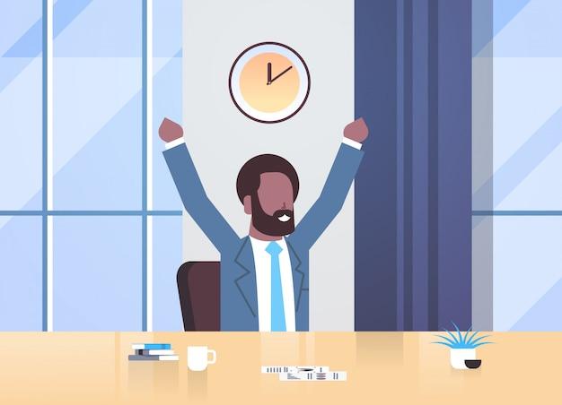 Hombre de negocios feliz levantando las manos expresando el éxito eficaz gestión del tiempo concepto hombre de negocios sentado lugar de trabajo moderno oficina interior retrato horizontal