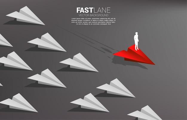 El hombre de negocios que se coloca en el aeroplano de papel rojo del origami se mueve más rápido que el grupo de blanco concepto de negocio de carril rápido para movimiento y comercialización