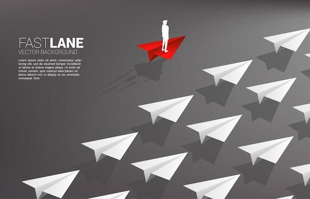 El hombre de negocios que se coloca en el aeroplano de papel rojo del origami se mueve más rápido que el grupo de blancos.