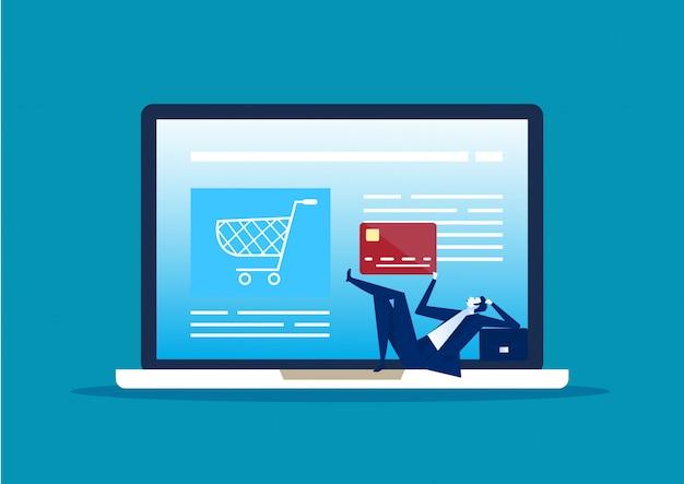 Hombre de negocios que se sienta en la tarjeta de crédito plástica que mira la pantalla de la computadora, muchacho con el dinero