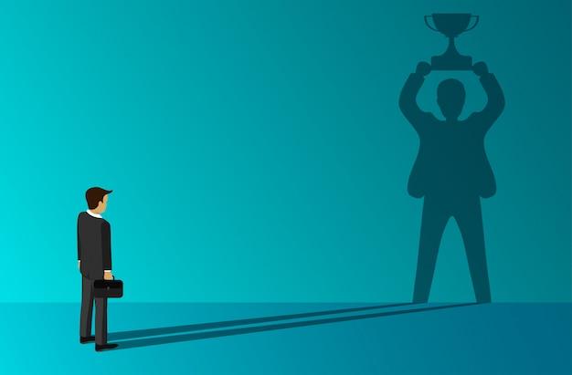 Hombre de negocios que una sombra de pie sosteniendo un trofeo de éxito en la pared