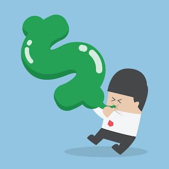 Hombre de negocios que sopla aire en globo de forma de dólar