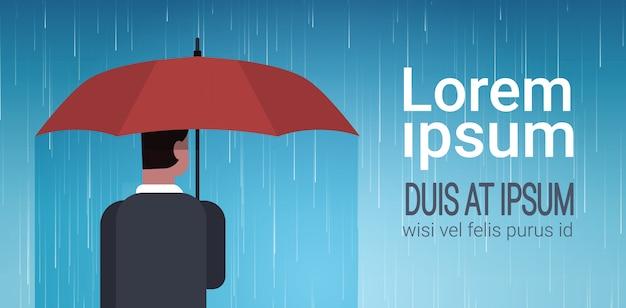 Hombre de negocios que sostiene el concepto de la protección de la vista posterior de la parte posterior del fondo de la lluvia enorme de unger del paraguas