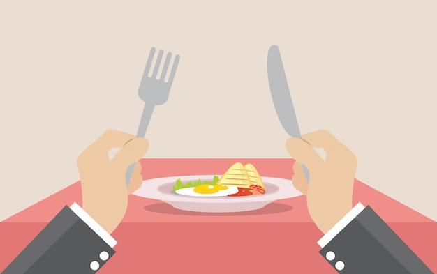 Hombre de negocios que sostiene el cuchillo y la bifurcación para comer el desayuno en el plato.