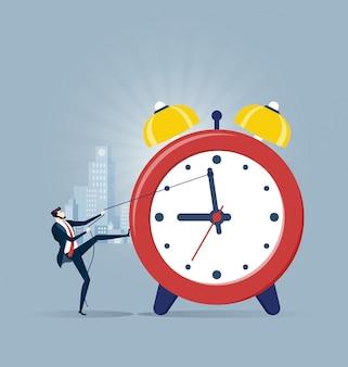 Hombre de negocios que tira del reloj en concepto de gestión de tiempo