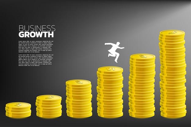 Hombre de negocios saltar a una columna más alta de dinero gráfico.