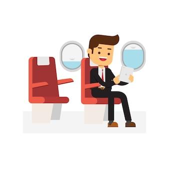 Hombre de negocios sentado en el avión y sosteniendo su tableta