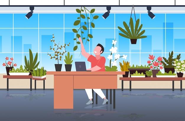 Hombre de negocios sentado en un lugar de trabajo cómodo con plantas en macetas ambiente doméstico concepto de oficina verde