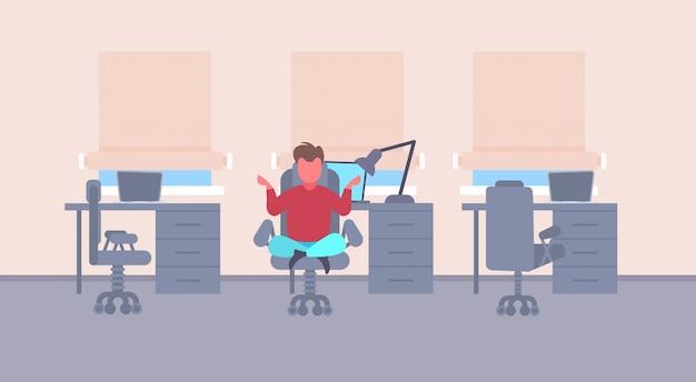 Hombre de negocios, sentado, postura de loto, en, calma, hombre de negocios, relajante, meditación, trabajando, alivio del estrés, concepto, moderno, oficina, interior, plano, horizontal