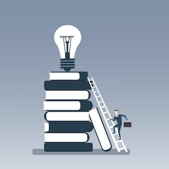 Hombre de negocios subir libros pila de encender foco en la parte superior