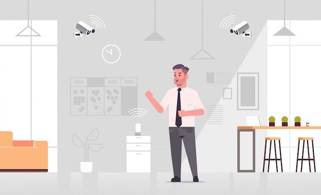 Hombre de negocios usando una cámara cctv controlada por reconocimiento de voz de altavoz inteligente