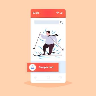 Hombre obeso gordo esquiador realizando ocio activo en la temporada de invierno chico con sobrepeso esquí concepto de pérdida de peso pantalla del teléfono inteligente aplicación móvil en línea