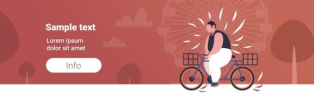 Hombre obeso gordo montando bicicleta sobrepeso chico ciclismo bicicleta concepto de pérdida de peso parque de verano rueda de la fortuna copia espacio