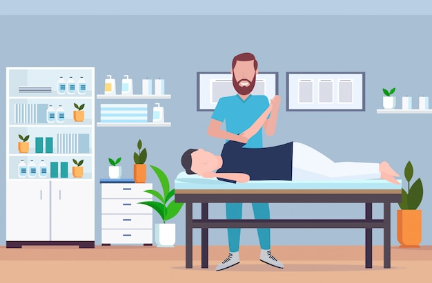 Hombre paciente acostado en la mesa de masaje terapeuta haciendo tratamiento curativo masaje mano lesionada manual fisioterapia rehabilitación concepto integral moderno hospital oficina interior horizontal