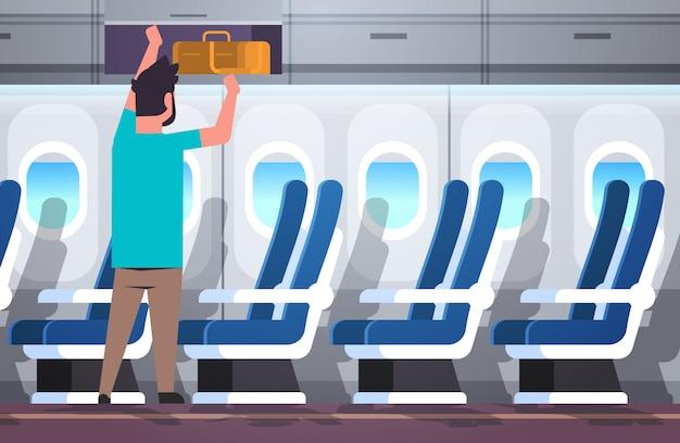 Hombre pasajero poniendo equipaje en el estante superior concepto de vacaciones de viaje avión moderno tablero interior plano horizontal de longitud completa