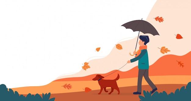 Hombre paseando al perro en otoño.