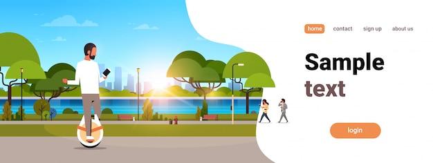 Hombre paseo mono rueda eléctrica con smartphone