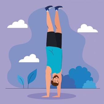 Hombre de pie en las manos al aire libre, ejercicio de recreación deportiva