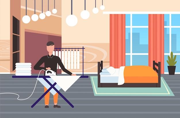 Hombre planchando ropa chico usando hierro haciendo tareas domésticas concepto moderno dormitorio interior masculino personaje de dibujos animados de longitud completa horizontal