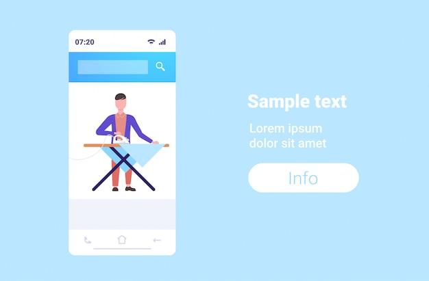 Hombre planchando ropa chico usando hierro haciendo tareas domésticas concepto smartphone pantalla en línea aplicación móvil personaje de dibujos animados masculino espacio integral copia horizontal