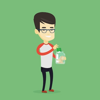 Hombre poniendo dinero en dólares en frasco de vidrio.