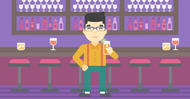 Hombre que bebe el cóctel anaranjado en la barra.