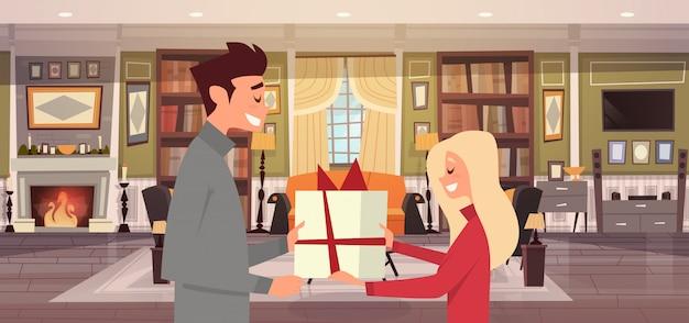 Hombre que da a la mujer la caja actual sobre el fondo de la sala de estar, feliz pareja celebra las vacaciones en casa