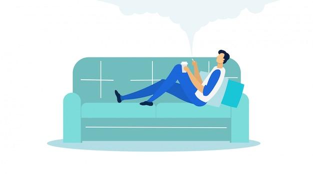 Hombre que miente en el sofá que sostiene la taza y que fuma plano.
