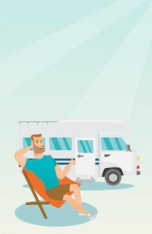 Hombre que se sienta en una silla delante de la autocaravana.