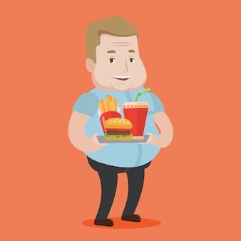 Hombre que sostiene la bandeja llena de comida rápida.