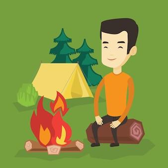 Hombre sentado en el registro cerca de la fogata en el camping.
