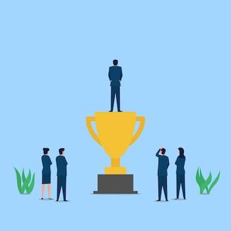 El hombre se para sobre el trofeo mientras otros ven una metáfora del éxito y el reconocimiento.