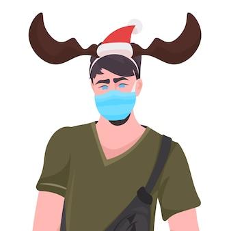 Hombre con sombrero festivo con máscara para prevenir la pandemia de coronavirus año nuevo navidad