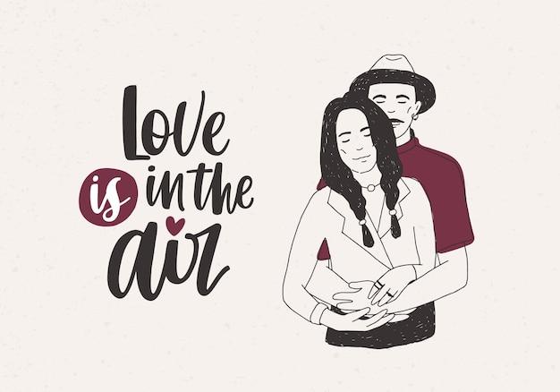 Hombre con sombrero de pie detrás de una mujer con trenzas y abrazándola y love is in the air letras en blanco