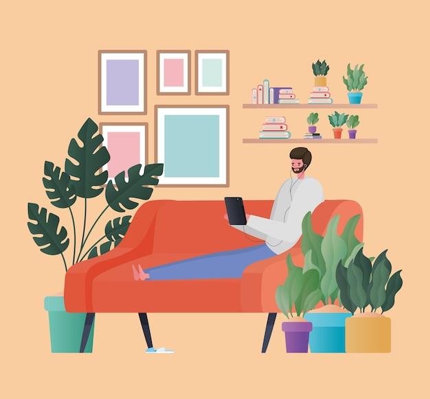 Hombre con tableta trabajando en el diseño del sofá naranja del tema trabajo desde casa
