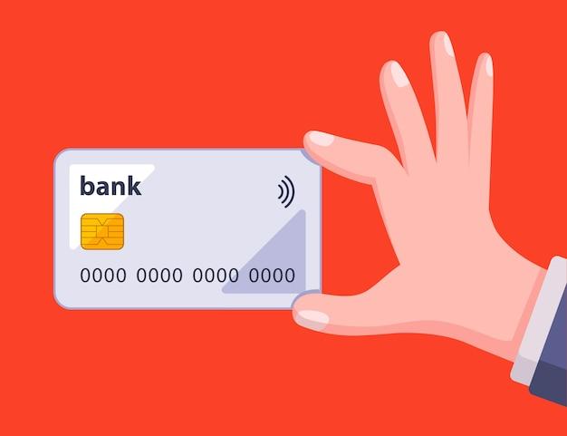 El hombre tiene una tarjeta bancaria en la mano sobre un fondo rojo.