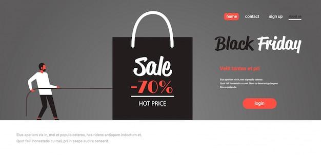 Hombre tirando de la bolsa de compras con gran cartel de venta oferta especial de descuento de promoción de vacaciones de venta especial de viernes negro